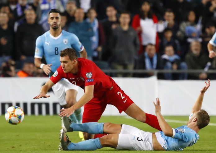 Poland's midfielder Krystian Bielik (C) falls over Israel's midfielder Dan Leon Glazer (bottom) as they vie for the ball during the EURO 2020 group G qualifiers football match between Israel and Poland at the Teddy stadium in Jerusalem on November 16, 2019.